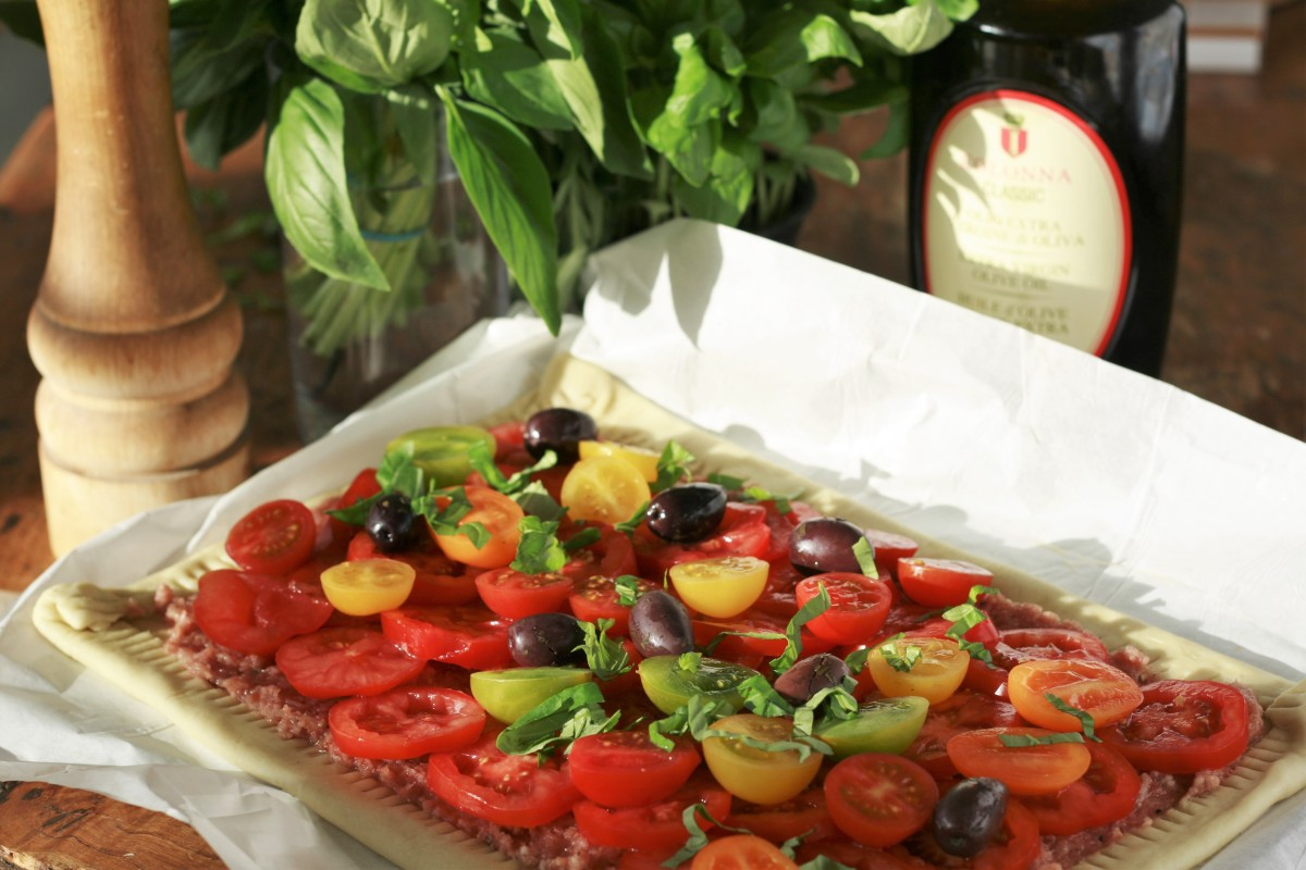 Tomato and prosciutto tart with scattered basil and olives