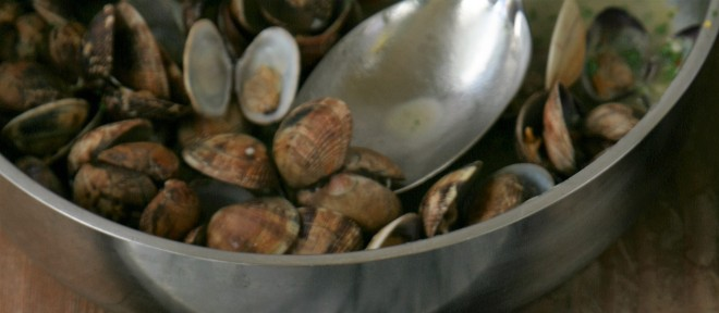 Cooked clams reheating in the lemon butter sauce