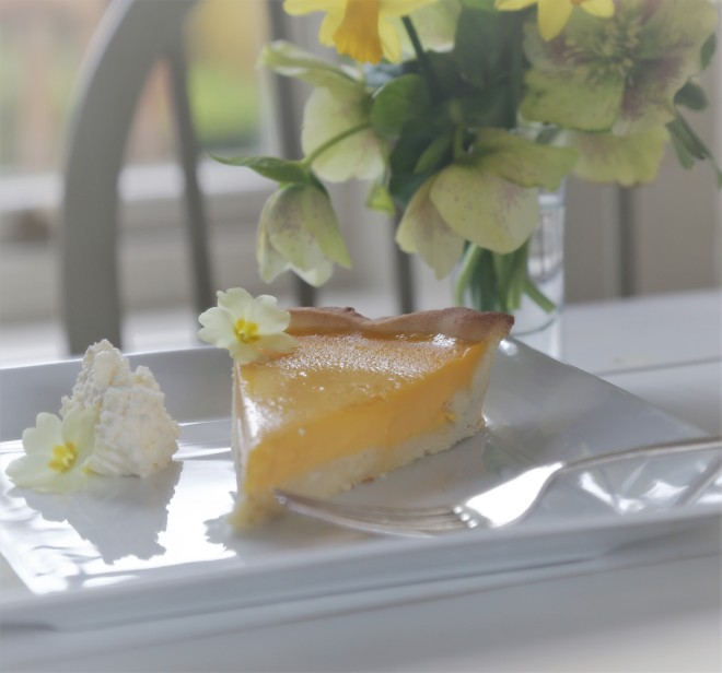 passionfruit tart with spring flowers and sunshine